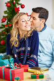 Man kissing woman while she wraps christmas gifts Royalty Free Stock Photos