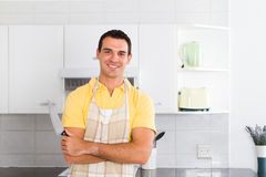 Man in kitchen. Happy young man with apron in modern kitchen Royalty Free Stock Photo