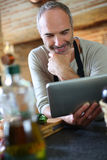 Man in kitchen checking recipe on internet Stock Image