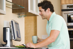 Man in kitchen with coffee using computer Stock Photo