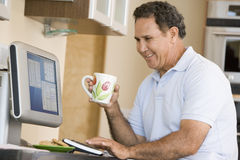 Man in kitchen with computer and coffee smiling Royalty Free Stock Images