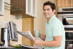 Man in kitchen with computer holding newspaper Stock Photography