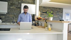 Man at kitchen countertop working on laptop from home stock footage