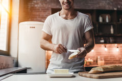 Man on kitchen. Cropped image of handsome man on kitchen is smearing butter on bread Royalty Free Stock Photo
