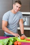 Man in the kitchen cutting tomatoes for salad Stock Photos
