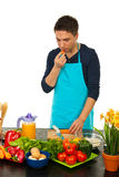 Man in kitchen eating carrot Stock Images