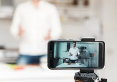 Man on the kitchen filming video. Vlogging concept royalty free stock photography