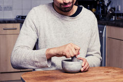 Man in kitchen is grinding spices Stock Photography