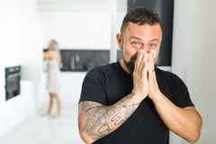 Man in kitchen having hay fever. Using tissue paper to clear nose royalty free stock photos