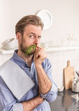 Man in the kitchen holding dill next to his nose as mustache Royalty Free Stock Photos