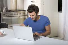 Man in the kitchen with laptop Royalty Free Stock Photos