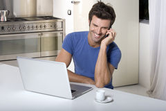 Man in the kitchen with laptop Stock Images