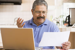 Man in kitchen with laptop and paperwork Royalty Free Stock Photos