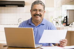Man in kitchen with laptop and paperwork smiling Stock Photos
