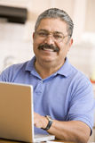 Man in kitchen with laptop smiling stock photography