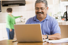Man in kitchen with laptop smiling Stock Image