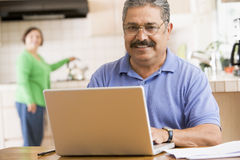 Man in kitchen with laptop smiling Royalty Free Stock Photo