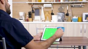 Man at the kitchen looking at digital tablet PC stock video