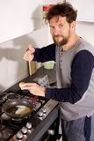 Man in kitchen in the morning cooking eggs ok sign stock images