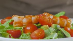 A man in the kitchen prepares a salad of avocado, zucchini and cherry tomatoes and puts large appetizing shrimps on top. A man in the kitchen prepares a salad stock video footage
