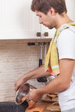 Man at the kitchen. Man preparing breakfast at the kitchen Royalty Free Stock Images