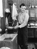 Man in a kitchen pumping water Royalty Free Stock Image