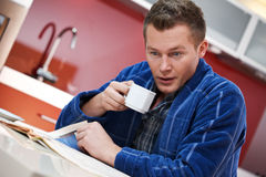 Man in kitchen reading newspaper Stock Photo