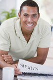 Man in kitchen reading newspaper and smiling Stock Images