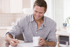 Man in kitchen reading newspaper and smiling Stock Photos