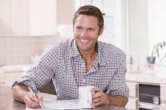 Man in kitchen reading newspaper and smiling Royalty Free Stock Photo