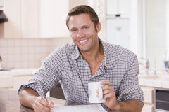 Man in kitchen reading newspaper and smiling Royalty Free Stock Photos