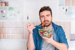 Man in the kitchen ready to eat vegetables royalty free stock image