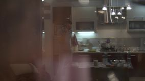 A man in the kitchen speaks on a cell phone. Walking in the kitchen and solving problems. stock video footage