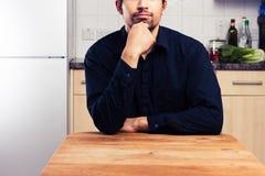 Man at kitchen table thinking Royalty Free Stock Photos