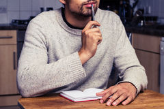 Man in kitchen is thinking and writing Royalty Free Stock Photo