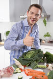 Man in the kitchen with thumb up preparing dinner. Stock Images