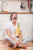 Man at the kitchen. Tired man sitting on the floor at the kitchen Royalty Free Stock Photography