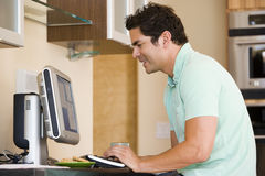 Man in kitchen using computer and smiling Stock Photography