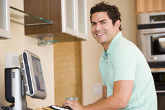 Man in kitchen using computer and smiling Royalty Free Stock Photo