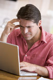 Man in kitchen using laptop frowning Royalty Free Stock Photos