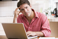 Man in kitchen using laptop frowning Stock Image