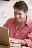 Man in kitchen using laptop smiling Royalty Free Stock Image
