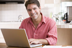 Man in kitchen using laptop smiling Royalty Free Stock Photo