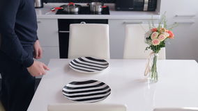 Man in the kitchen yourself serves white table for two persons. On the surface, on which stands a little delicate bouquet of flowers in a glass vase, Male puts stock video footage