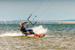 Man kitesurfer rides kite splashing on Bugaz firth at Black Sea coast on sunny day having fun and showing sign royalty free stock image