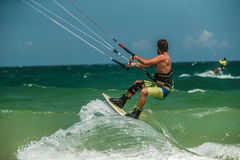 Man Kitesurfing in blue sea Stock Images