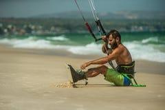 Man Kitesurfing. Handsome man sitting on the beach and preparing to Kitesurfing Stock Images