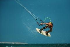 Man Kitesurfing i det blåa havet Royaltyfria Bilder