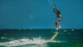 Man Kitesurfing i det blåa havet Arkivbild