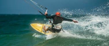Man Kitesurfing i det blåa havet Arkivfoto